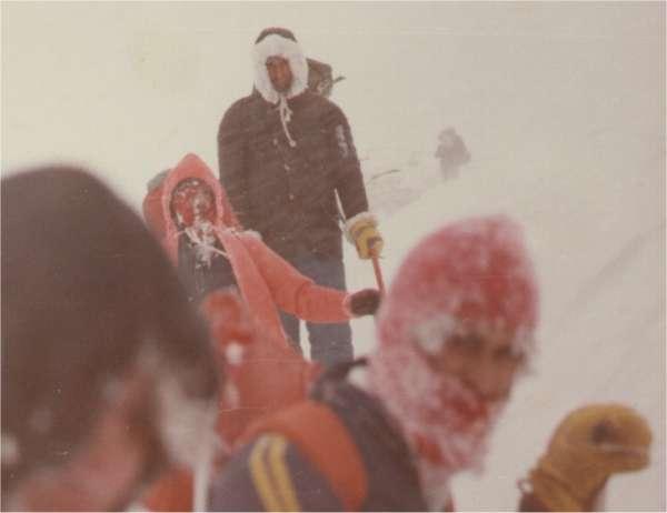 """Φωτογραφία ντοκουμέντο: Σάββατο 24 Δεκεμβρίου 1979, απόγευμα στο """"Λαιμό της Σκούρτας"""". Η ομάδα έχει ήδη χάσει δύο από τα μέλη της. Οι υπόλοιποι συνεχίζουν την δραματική πορεία προς τη σωτηρία τους ενώ η χιονοθύελλα μαίνεται ακόμα. Σε πρώτο πλάνο (από αριστερά): Χατζηλαζάρου, Αναγνώστου. Σε δεύτερο πλάνο: Ξινογιαννακόπουλος, Μυστακίδης (όρθιος). Στο βάθος ο Βασιλακάκης. (Φωτογραφία Ζ. Τρόμπακας)"""