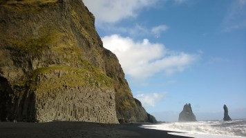Basalt columns at Reynisfjara with Reynisdrangur sea stacks.