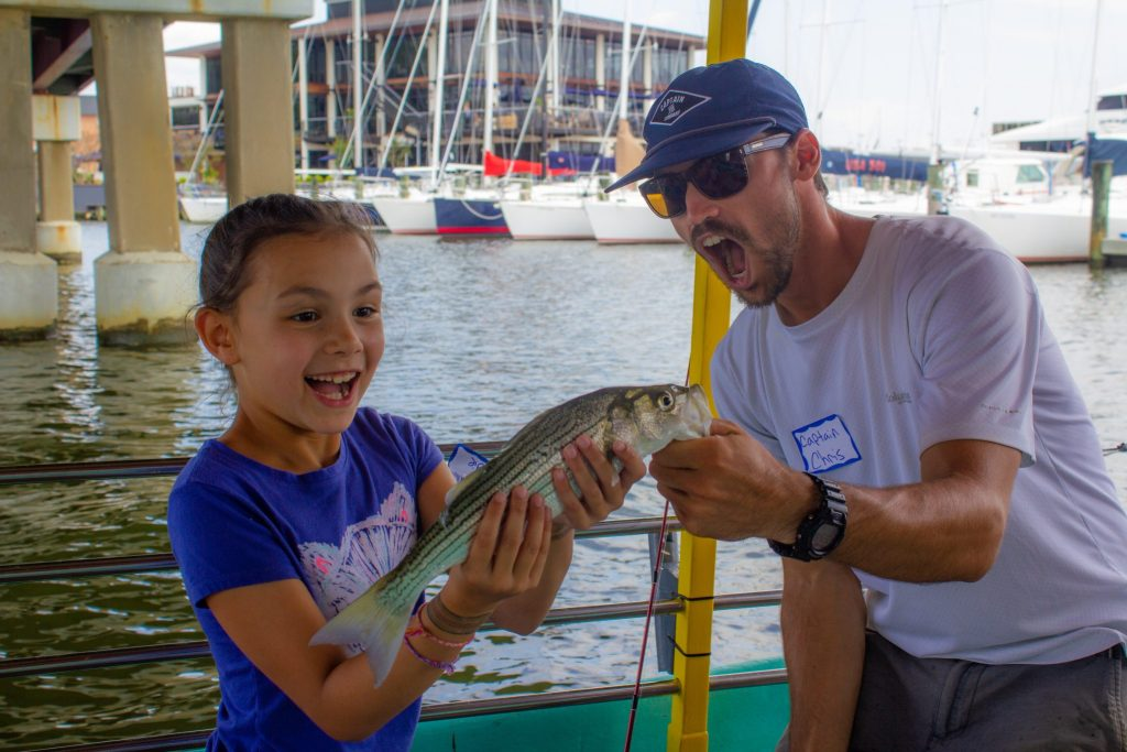 girl excited to catch big rockfish on family fishing boat