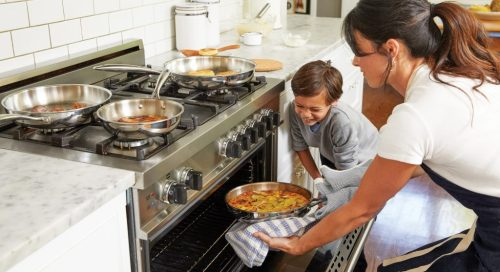 Woman and boy putting pan into oven