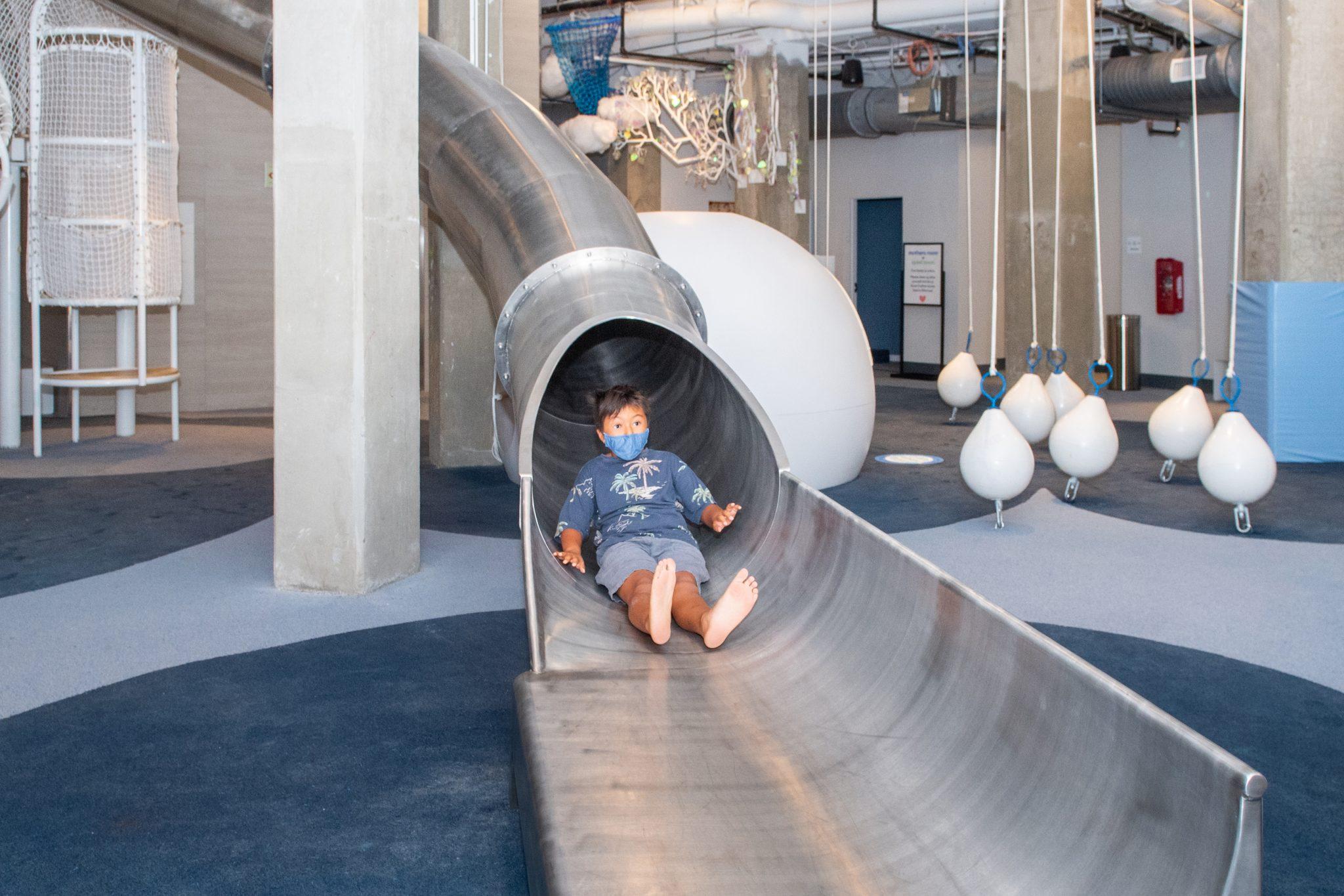 boy at bottom of metal slide