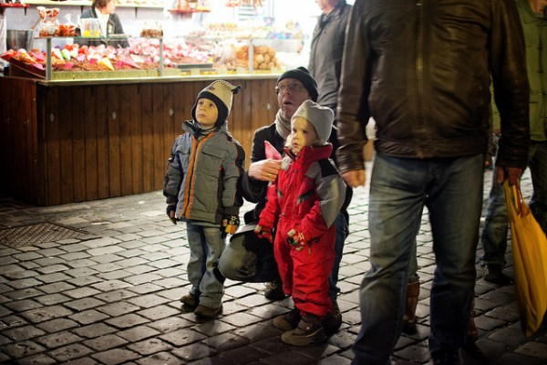 """This shot is from Nuremberg, Germany during the Christmas Market festivals last year. We just couldn't ignore this father and his kids who were awestruck by the astronomical clock in the town square."""