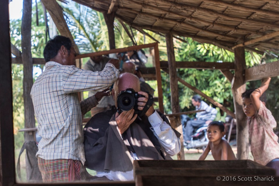 The neighborhood kids watch as the 'barring' with a camera gets his haircut.