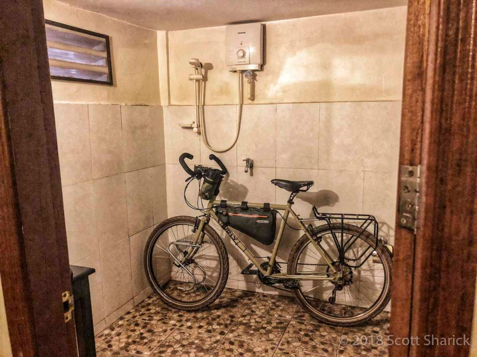 My bicycle sits in the shower of my guesthouse after a few days of dusty riding.