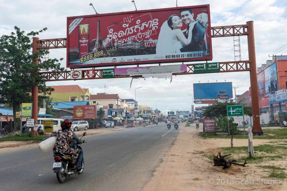 Traffic in a city along a two lane road in Cambodia on my Strokes to Spokes bicycle ride