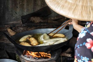 A Vietnamese woman tends to frying bananas in hot oil over an open fire.