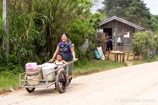 A Laotian mother transports her goods and child in a two wheeled cart in a small village of the northern Laos mountains.