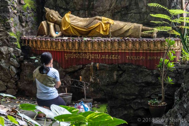 A woman prays in front of a golden reclining Buddha in Laos.
