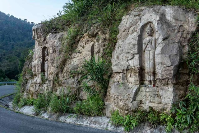 Carvings of Buddhas along the side of the road on The Loop in Laos.
