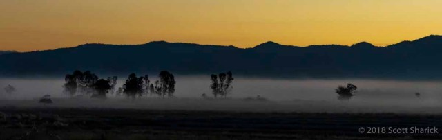 Mist covers the valley with the mountains in the distance at sunrise.