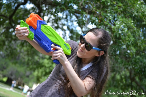 action shot during a water gun photo shoot- perfect for couples, newly engaged or married couples to do! Make your engagement photos memorable with this fun water gun photoshoot idea! Perfect couple photo idea that makes for a great engagement photo idea! More over at adventuresofb2.com