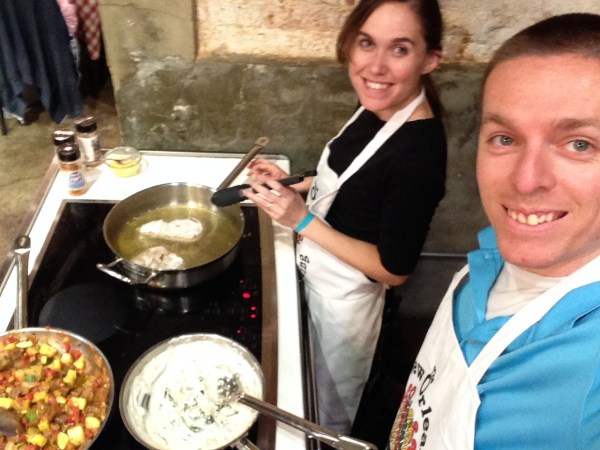 A couple at the new orleans school of cooking for a date night of cooking with a chef.