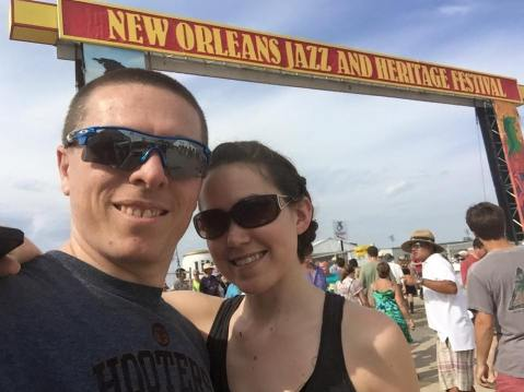 A couple in front of the jazz fest sign in new orleans. A fantastic festival that offers music, food and gifts which makes it one of the best kind of date night ideas.