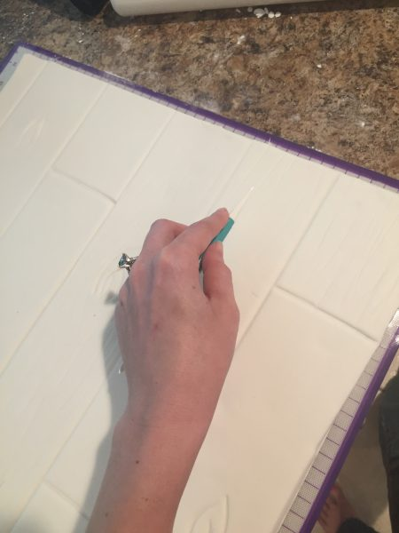 Using wilton's decorating tools to draw lines on fondant to make it look like a wood board