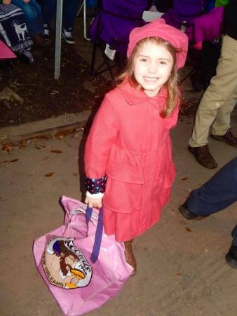 A little girl enjoying Mardi Gras parades in New Orleans. Learn how to make your trip with kids to Mardi Gras successful here. - adventuresofb2,com