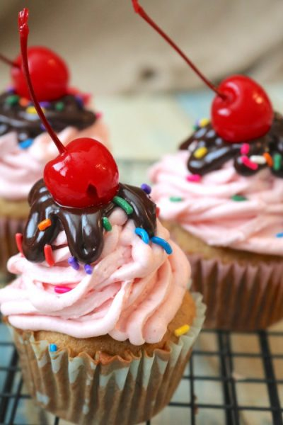 A classic dessert with a twist! Banana split cupcakes will wow any party guests with all the flavors of chocolate, strawberry and banana. A delicious banana split dessert where sharing is optional. - Adventuresofb2.com