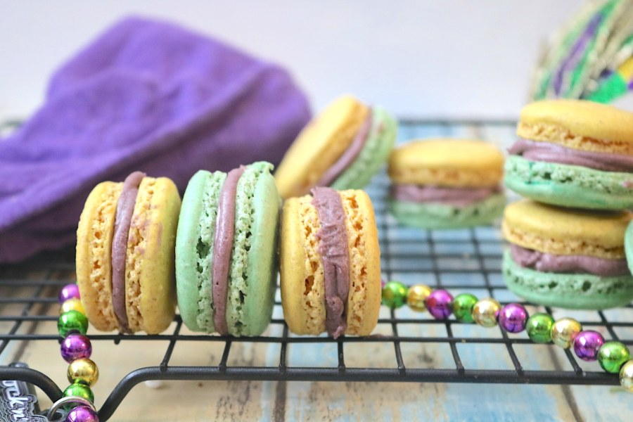 It's carnival time in New Orleans and what better way to celebrate than with Mardi Gras King Cake Macarons! The light fluffy macarons have flavors of cinnamon swirled with vanilla just like king cake. In festive purple, green, and gold colors, these will be the perfect little treat at your next Mardi Gras party! - AdventuresofB2.com