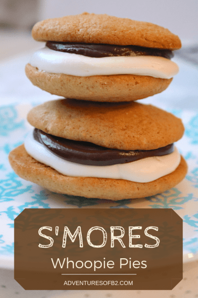 The ultimate way to eat a s'mores. S'mores Whoopie Pies are made of a soft graham cracker cookie with smooth chocolate ganache and fluffy marshmallow buttercream. Easy to make and kid approved, these will be the perfect winter dessert for cold nights! Pairs perfectly with a nice cup of hot coca- adventuresofb2.com #smores #cookies #whoopiepies #dessert