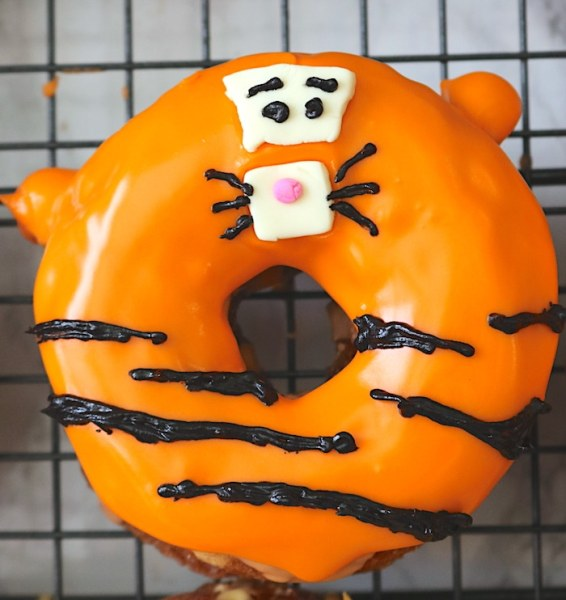 Last, add details to your Tigger donut! Make two small circles for the eyes and small lines for the eyebrows and whiskers. Then alternate small and long lines in a wavy pattern for the stripes. - Adventuresofb2.com