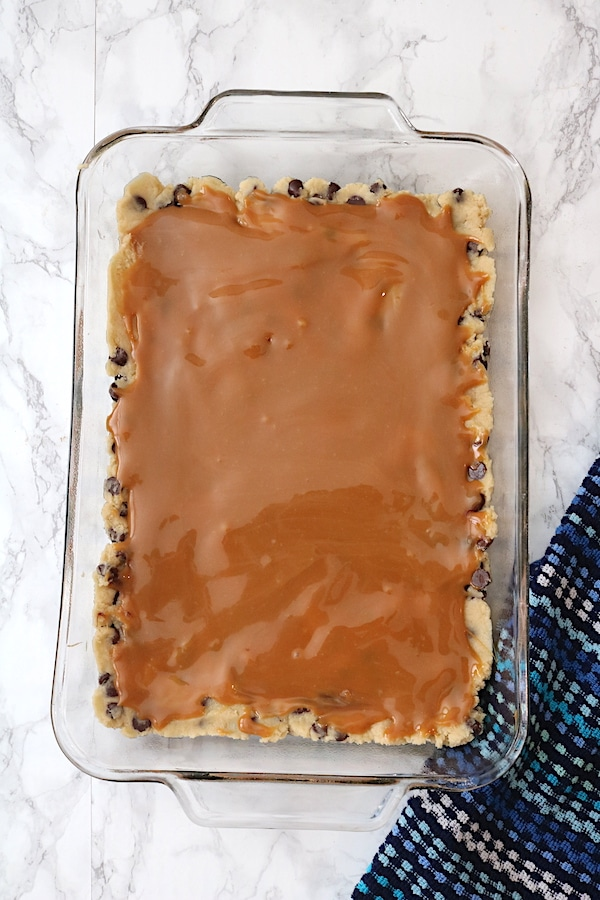 step 2 of making chocolate chip caramel bars - once you have a layer of your favorite chocolate chip cookie dough. It is time to add your layer of salted caramel sauce. How delicious and pretty does this dessert look? - adventuresofb2.com