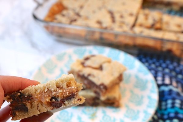 Rich, gooey chocolate chip salted caramel bars are every dessert lover's dream. So simple to make and yet undeniably delicious. Two layers of your favorite chocolate chip cookie dough with salted caramel sauce in the middle. The perfect dessert to satsify any sweet tooth.- adventuresofb2.com