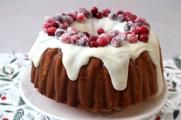 Sparkling cranberries decorate the top of this delicious white chocolate cranberry bundt cake. A festive holiday cake that will surely wow your guests at any party. A simple bundt cake filled with fresh cranberries topped with a white chocolate ganache and sugar cranberries. - adventuresofb2.com
