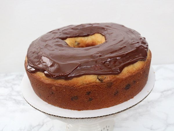 Look at all that chocolate frosting on top this giant doughnut cake. This delicious moist pound cake shaped like a big donut. A easy step by step tutorial on how to make a donut cake! - adventuresofb2.com