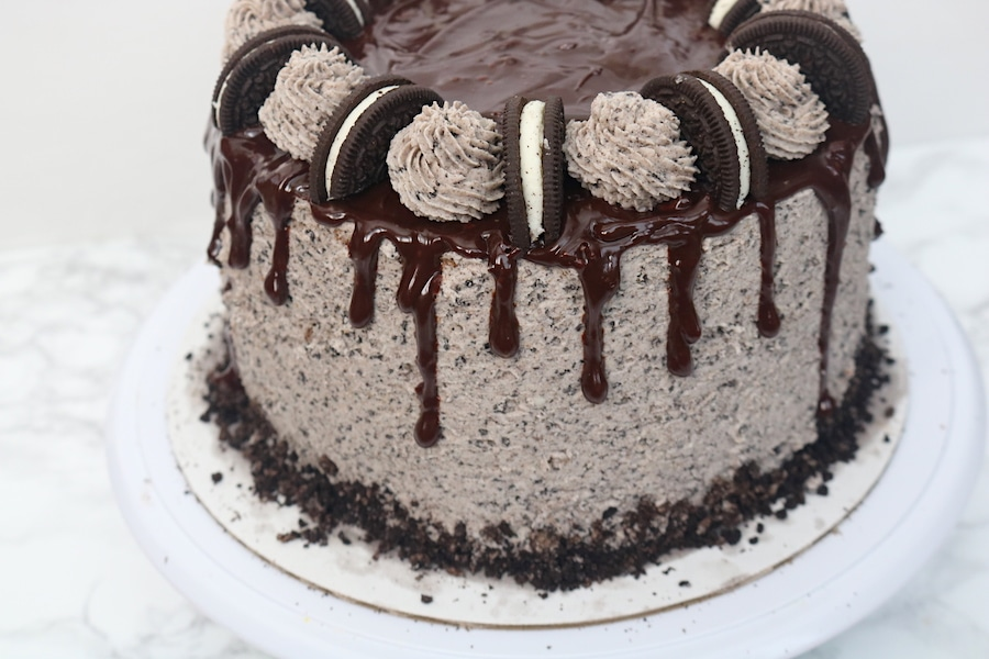 Oreo cookies and cream layer cake is the perfect celebration cake! It is loaded with Oreo cookies. It's a 3 layer simple white cake with bits of cookies and cream with oreo buttercream layered in between with chocolate ganache. It's every cookie lover's dream! - adventuresofb2.com