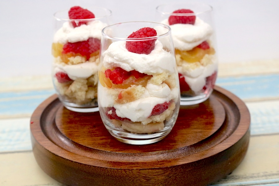 Mini Lemon Raspberry Trifles are the perfect dessert to bring to any party. Soft Layers of lemon raspberry cookies with lemon curd with raspberries and whip cream layered in between. Elegant individual mini desserts everyone will love! - adventuresofb2.com #minidesserts #trifles #lemonraspberry #raspberry #lemon