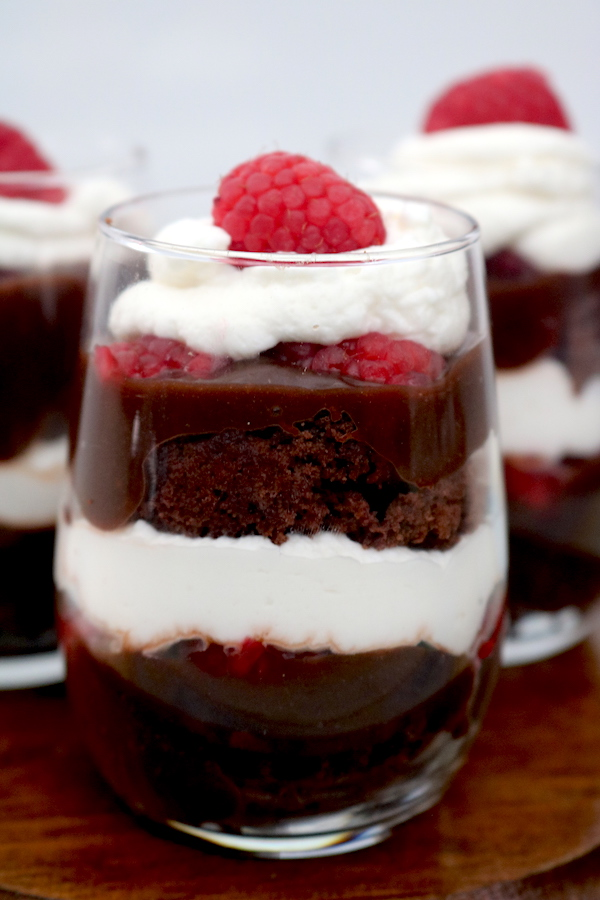 Chocolate Raspberry Brownie Trifles are the perfect dessert to bring to any party. Layers of fudgy brownie with chocolate pudding or chocolate raspberry ganache with raspberries and whip cream layered in between. Elegant individual mini desserts everyone will love! - adventuresofb2.com #minidesserts #trifles #chocolate #raspberry #brownie