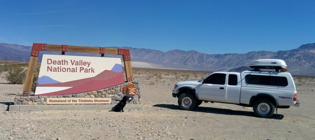 Willow and Tacoma in front of the Death Valley Entrance sign