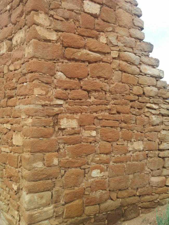 section of wall with small stones incorporated into the mud mortar