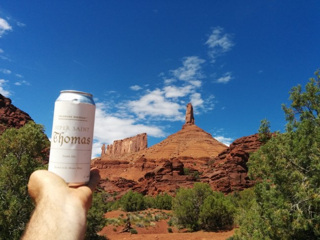 A Can of Fieldwork Super Saint Thomas held up with Castleton Tower and the Priest and Nuns rock formations in the background