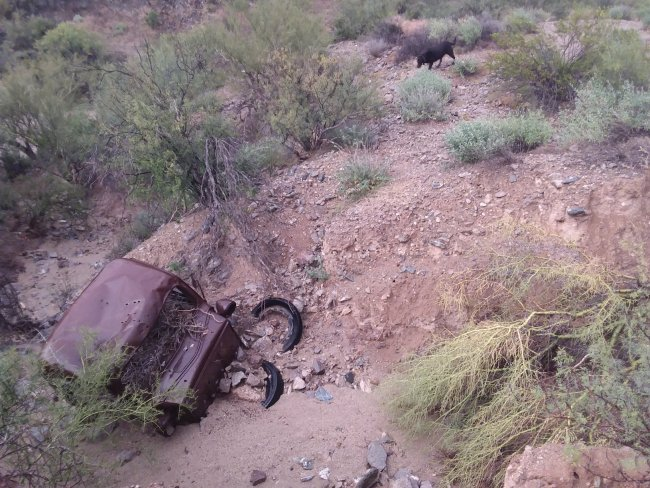 Old, rusted car down in the washed out road
