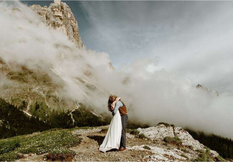 Elopement in the Italian Alps couple embraces on the top of a mountain with clouds all around them. Photo by Wild Connections Photography