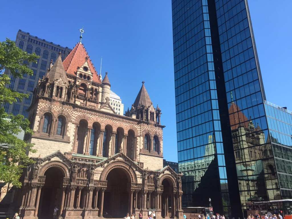 The church on Copley Square, Boston, a stone building with a red top, next to the glassy modern John Hancock tower.