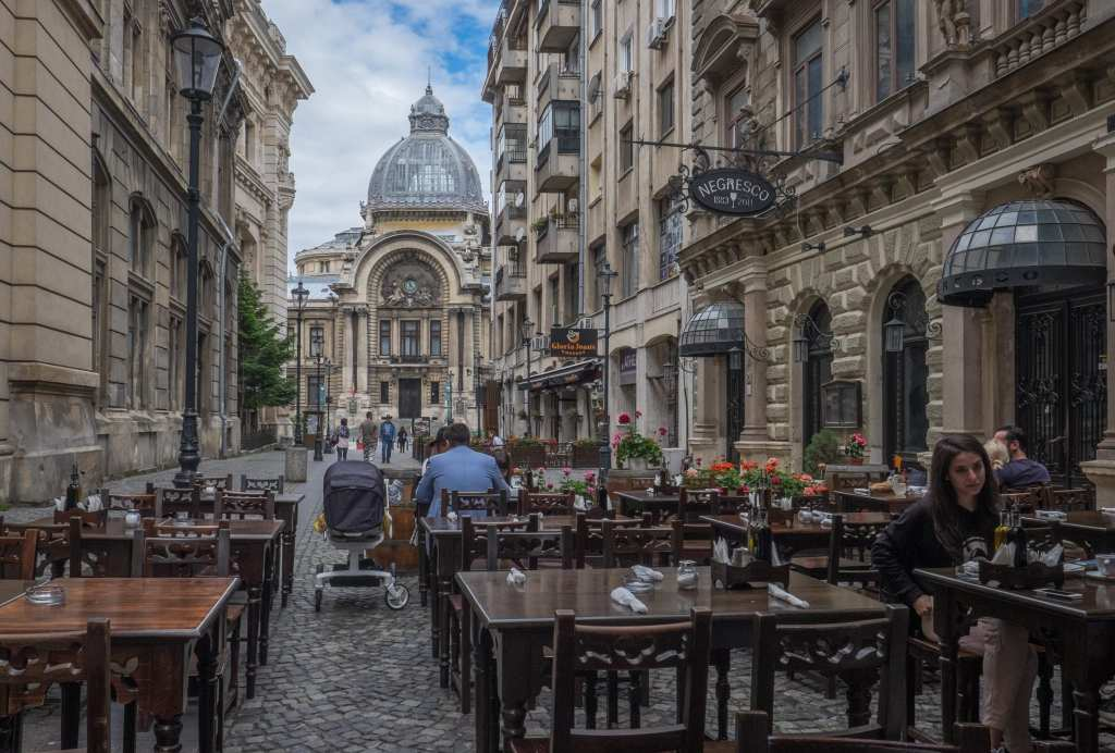 A domed church-like building in the distance in Bucharest, a street with sidewalk cafes in the foreground.