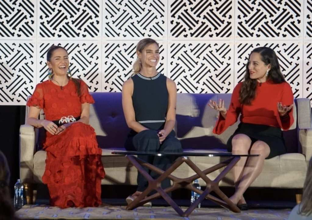 Kate speaking on a panel with two other women.
