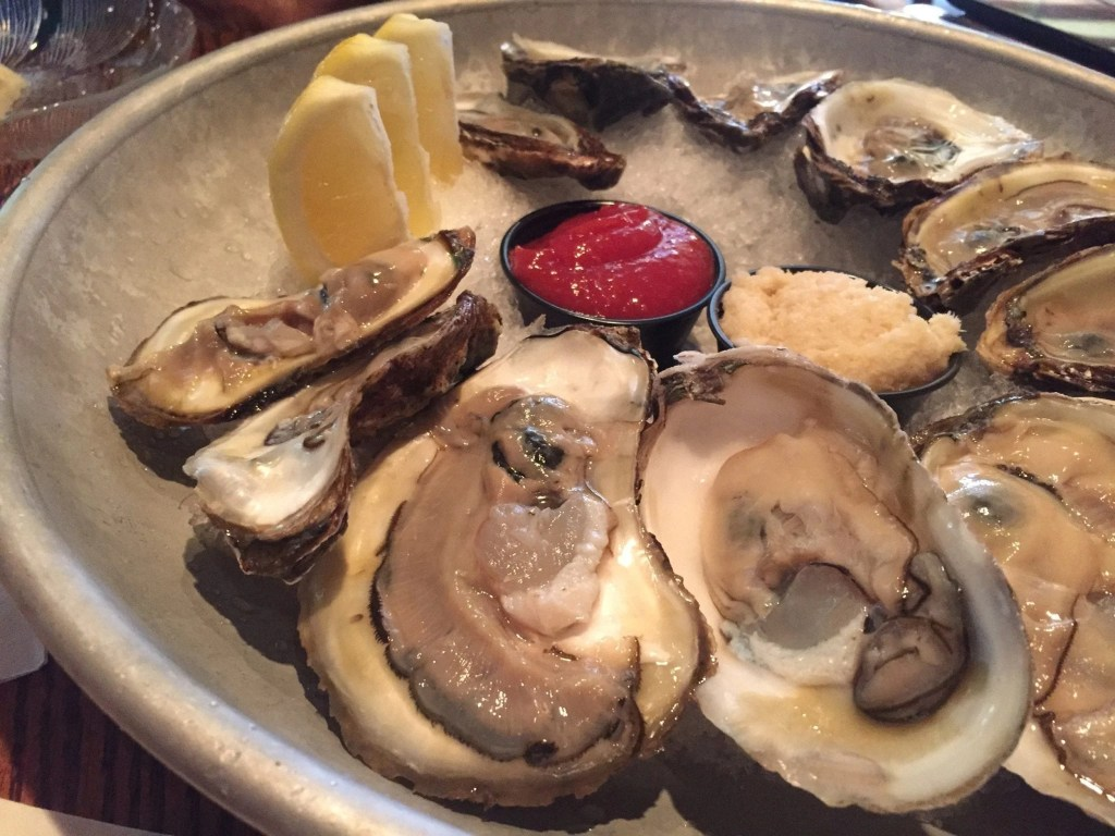 A plate filled with ice, oysters and lemon wedges on top.
