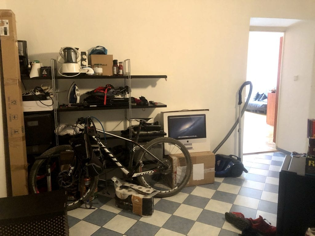 An entryway with cluttered open shelving and a bike and vacuum out in the open.