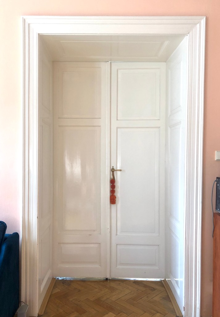 Glossy tall white wooden doors that have a small square entryway of their own. An orange poofed lanyard hangs on the door handle.