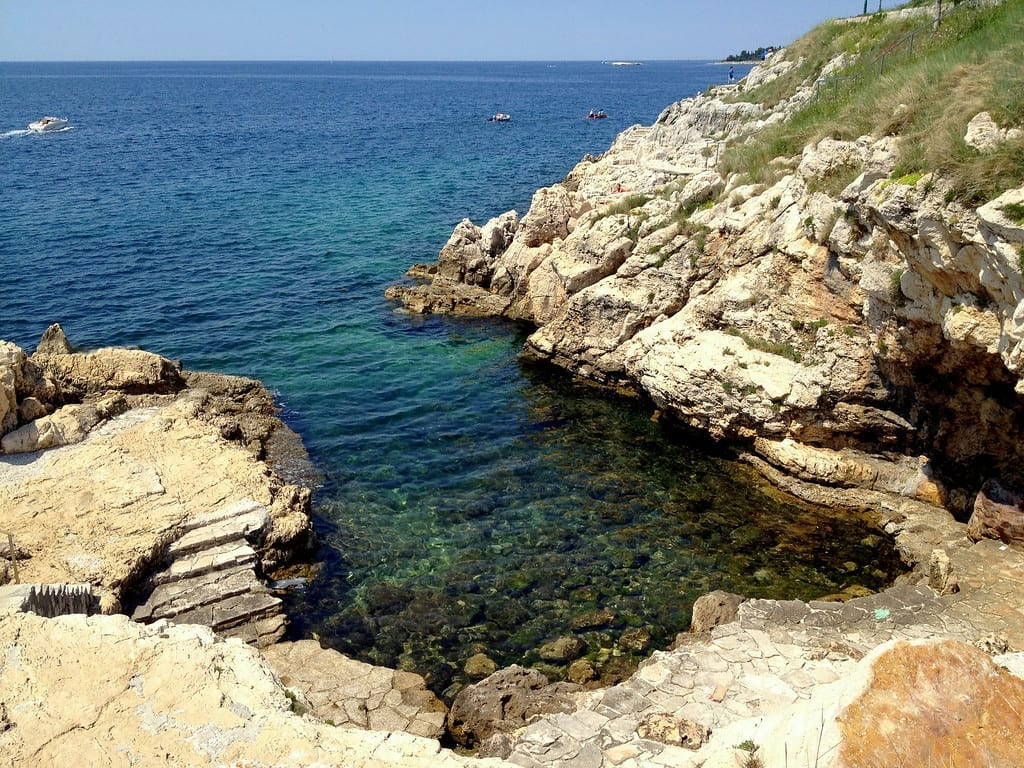 A small rocky bay with clear teal water in Rovinj.