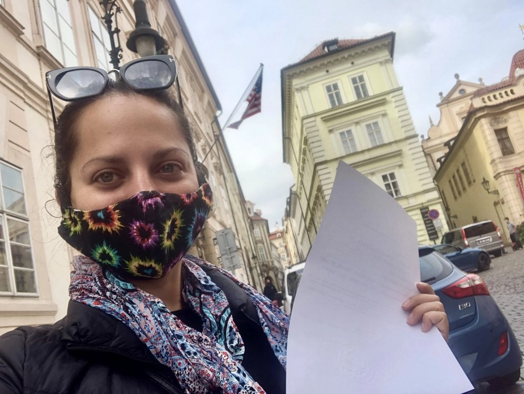 Kate wears a mask and stands in front of the US Embassy in Prague holding a piece of paper that was notarized