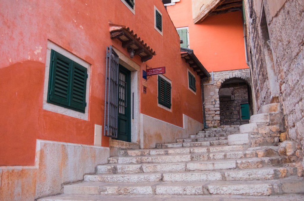 A stone staircase leading upward in Rovinj, surrounding walls are a deep earthy red shade.