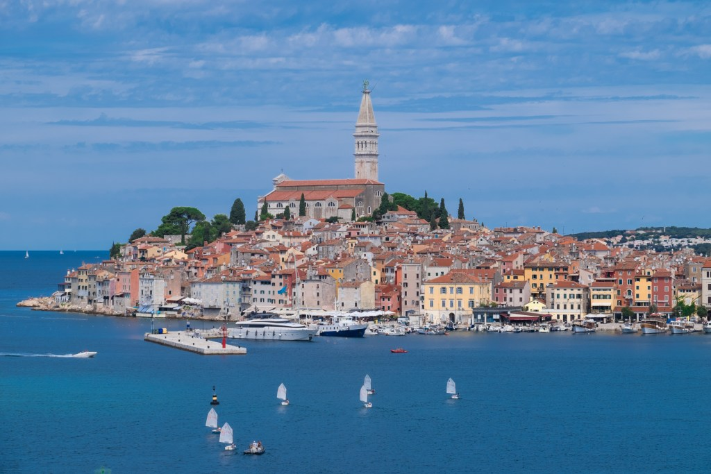 The Old Town of Rovinj, yellow and red-colored shuttered buildings with terra cotta roofs, a church steeple sticking straight up in the center, underneath a blue sky. Sailboats out in front of the old town.
