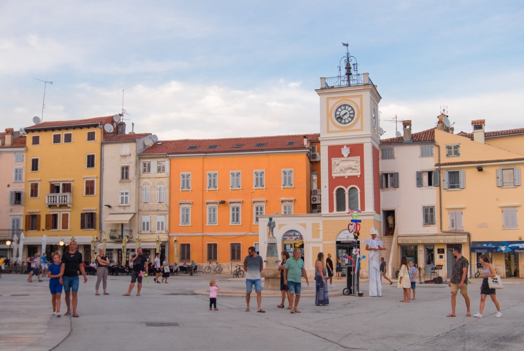 A town square with a yellow, red, and white clock tower, and street performers performing to a crowd.