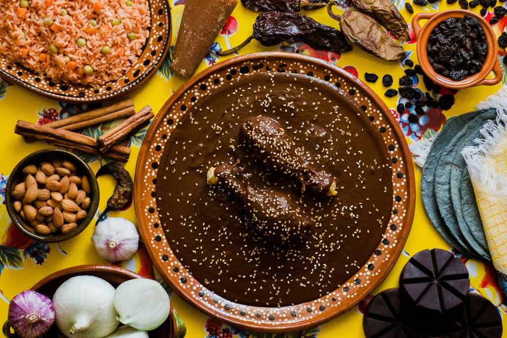 Several Oaxacan dishes on a yellow flowered tablecloth. In the middle is two pieces of chicken in a dark brown mole sauce with sesame seeds on top.