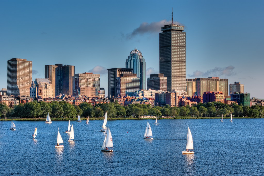 Sailboats cruise the Charles River with the Boston skyline in the background.