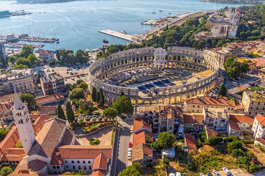 The ancient stone arena in Pula, Croatia, close to the sea. The photo is an aerial one and you see lots of terra cotta roofs and church steeples surrounding the arena.
