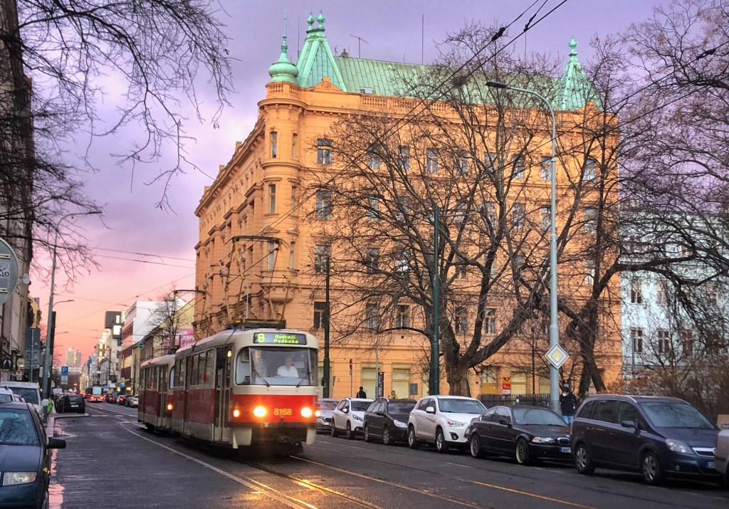 Prague in the evening: a tram comes down a street with its headlights on. In the background, a yellow building with a green roof, all set in front of an orange and purple sunset.
